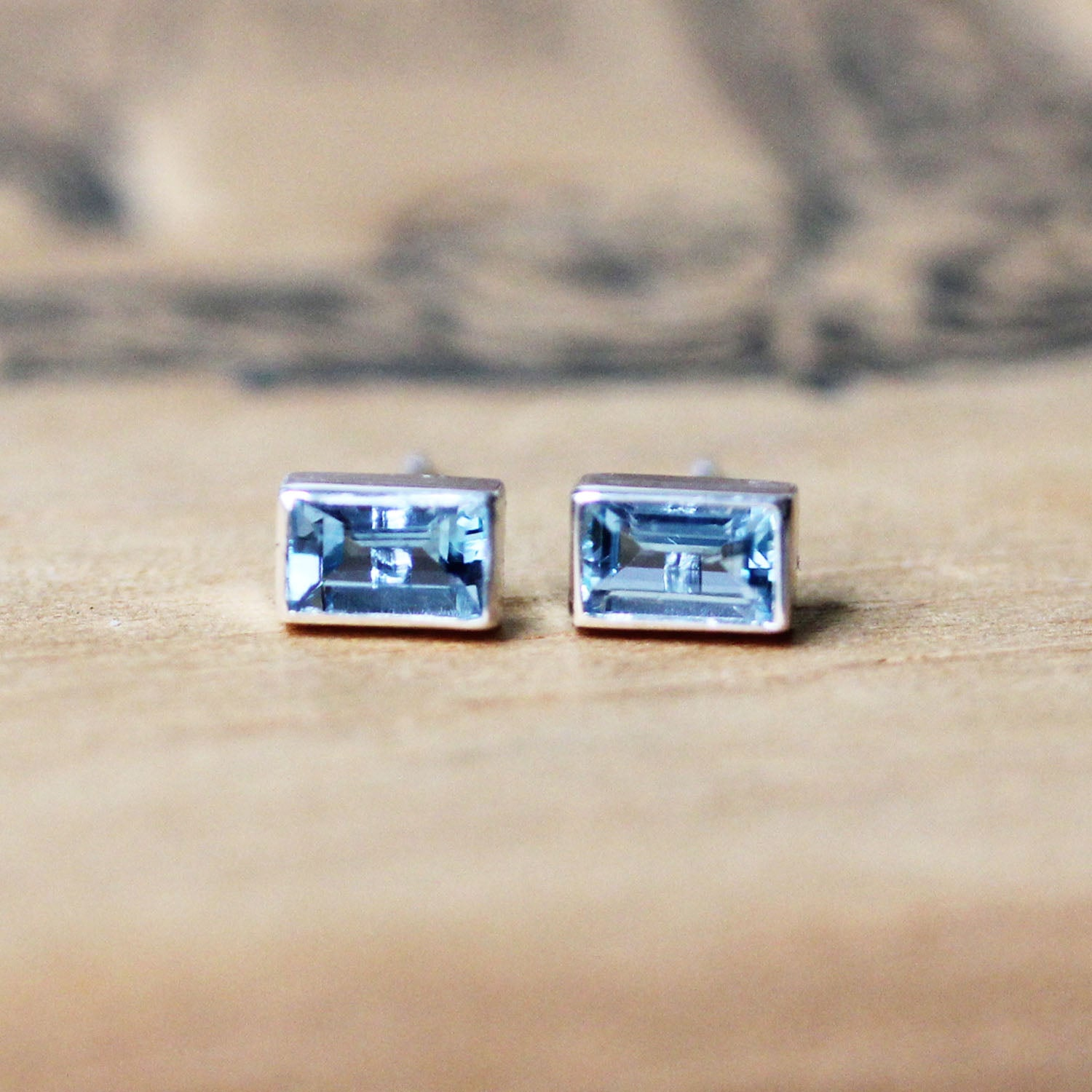 Sterling silver stud earrings with baguette cut aquamarine gemstones.