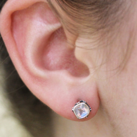 cushion shaped rainbow moonstone stud earrings on ear