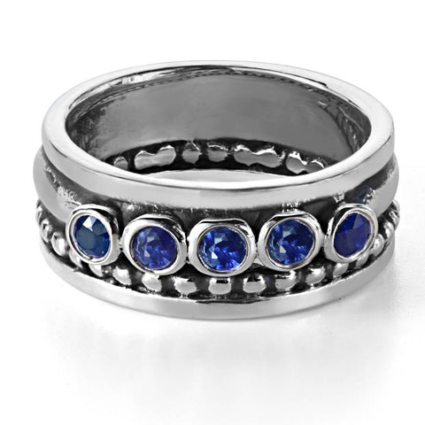 Wide band ring with five blue sapphire stones.