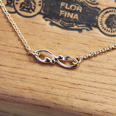 Infinity symbol necklace with bead detailing.