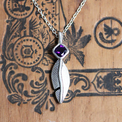 Sterling silver feather pendant necklace with amethyst gemstone.