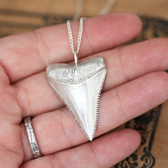 Sterling silver great white shark tooth from Metalicious resting on a hand