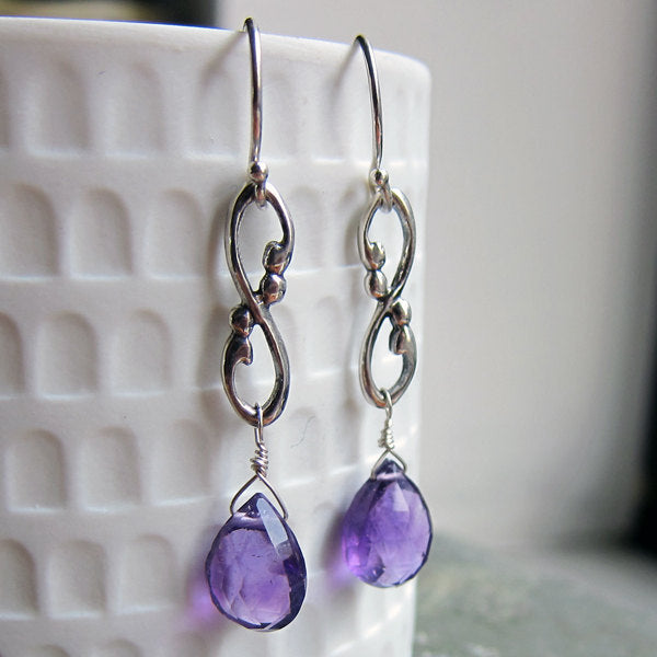 Sterling silver drop earrings featuring infinity signs and briolette cut amethyst gemstones.