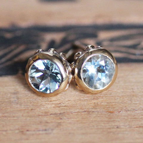 14k Gold stud earrings with blue aquamarine gemstones and unique detailing.