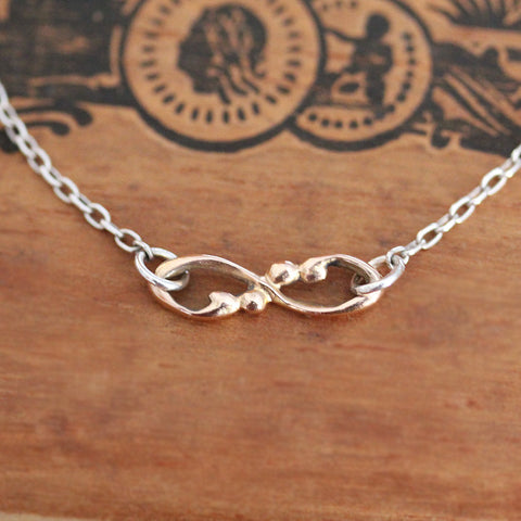 Rose gold infinity necklace with sterling silver chain.