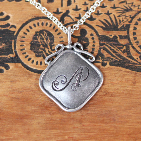 Sterling silver square with antique style initial engraved into pendant.