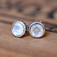 Front view of 5mm round rainbow moonstone stud earrings in sterling silver with beading around the sides