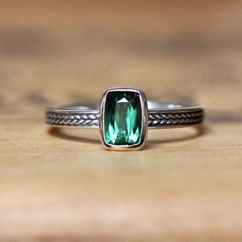 Sterling silver ring with braided band and cushion cut green tourmaline gemstone