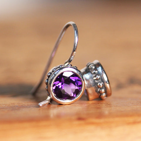 Sterling silver earrings with beading around a purple amethyst gemstone.