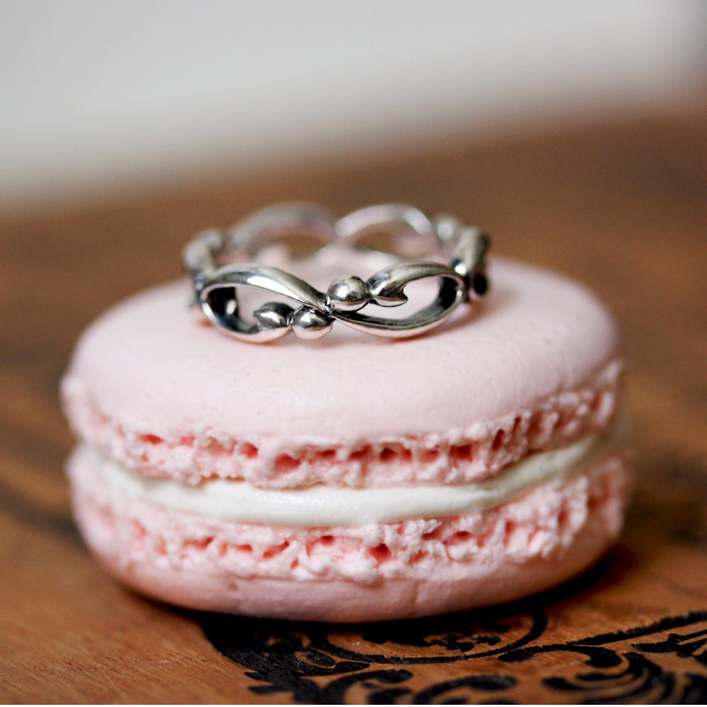 silver infinity filigree band sitting on a pink macaron