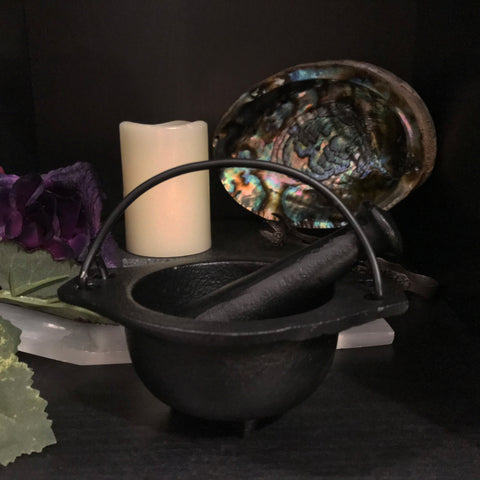 6Witch3 Cast Iron Cauldron with Pestle - Shown with the pestle resting in the bowl in front of a selenite incense burner, a candle, and an abalone shell.