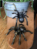 6Witch3 large iron spiders, one black with silver detail and one black with gold detail displayed next to a potted aloe on a wooden ironing board