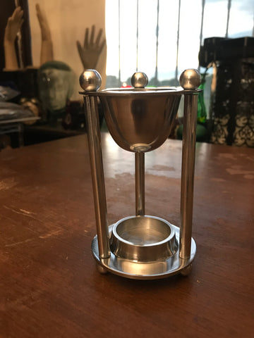 6Witch3 Hourglass Oil Burner - a silver oil diffuser sits on a wooden table, three pencil-thin columns with tiny pea-sized balls on top support a silver cup with a space at the base for a single tea light.