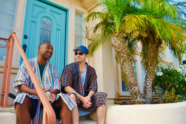 two men sitting on stoop wearing robe as swim cover up