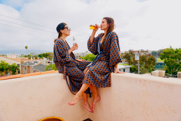 two women drinking a beer on a rooftop wearing robes as swim cover ups