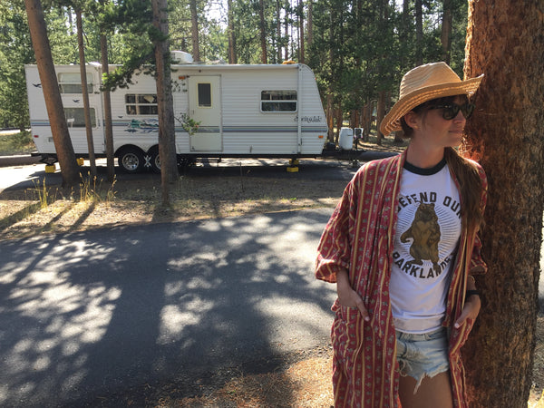woman at campsite standing in front of camper wearing a Highway Robery bathrobe