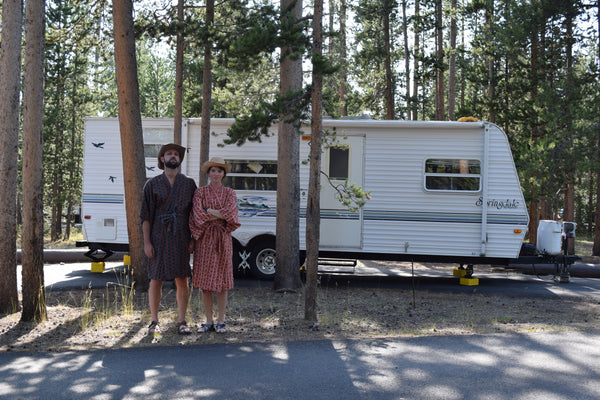 couple standing outside of rv in woods, wearing highway robery kimino robes annd cowboy hats