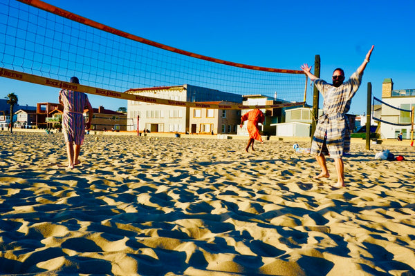 men playing beach volleyball wearing robes as swim cover ups