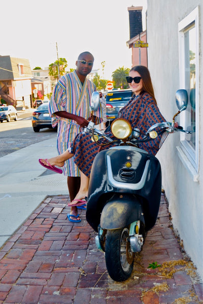 man and woman posing next to motorcycle wearing robes as swim cover ups