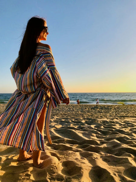 woman watching sunset wearing robe as a swim cover up