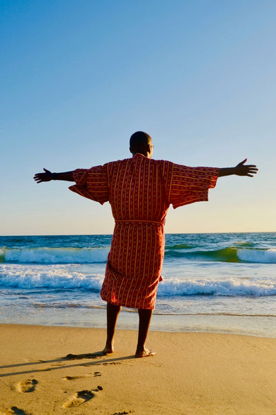 man dipping toes in ocean wearing robe as swim cover up