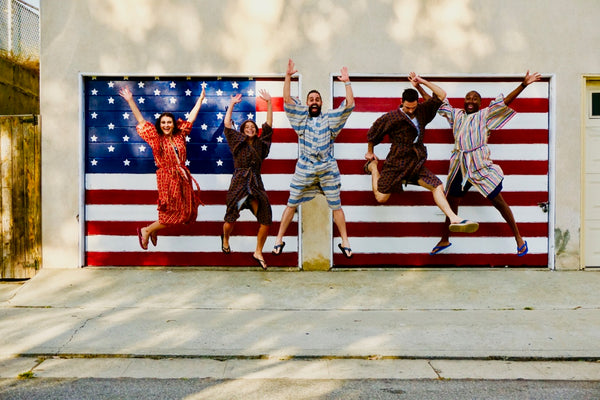 friends jumping in air in front of american flag wearing robes as a swim cover up