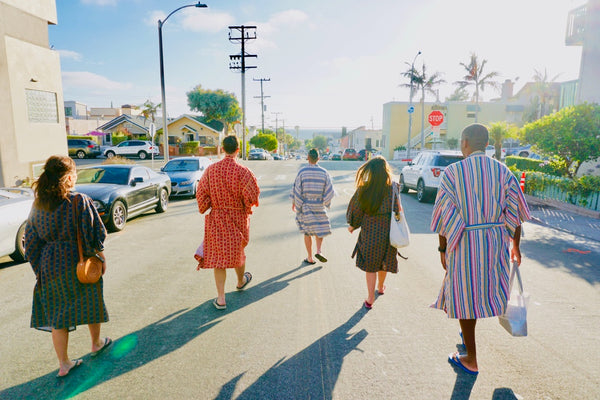 friends walking to beach wearing robes as swim cover up