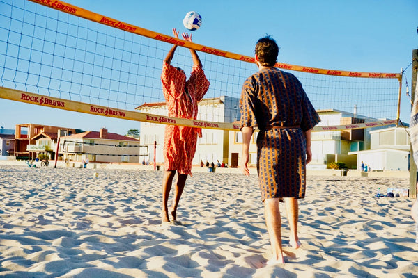 men playing beach volleyball wearing robes as swim coverups