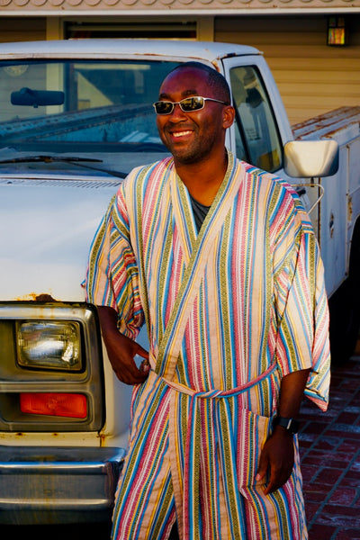 man posing next to truck weairng robe as swim cover up