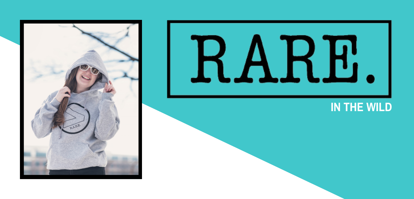 """On the left side of the image is a picture of Kristine taken outside. She is wearing a grey """"Greater than rare"""" hooded sweatshirt. On the right side of the image it has the words """"Rare. In the wild."""""""