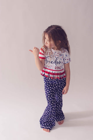 little girl with frizzy hair wearing the belltown bottoms in a patriotic stars print with a fringe t shirt.