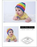 white baby wearing a rainbow beanie holding a blue pacifier
