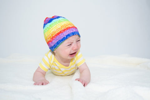 white baby wearing a rainbow beanie on a white blanket against a white background