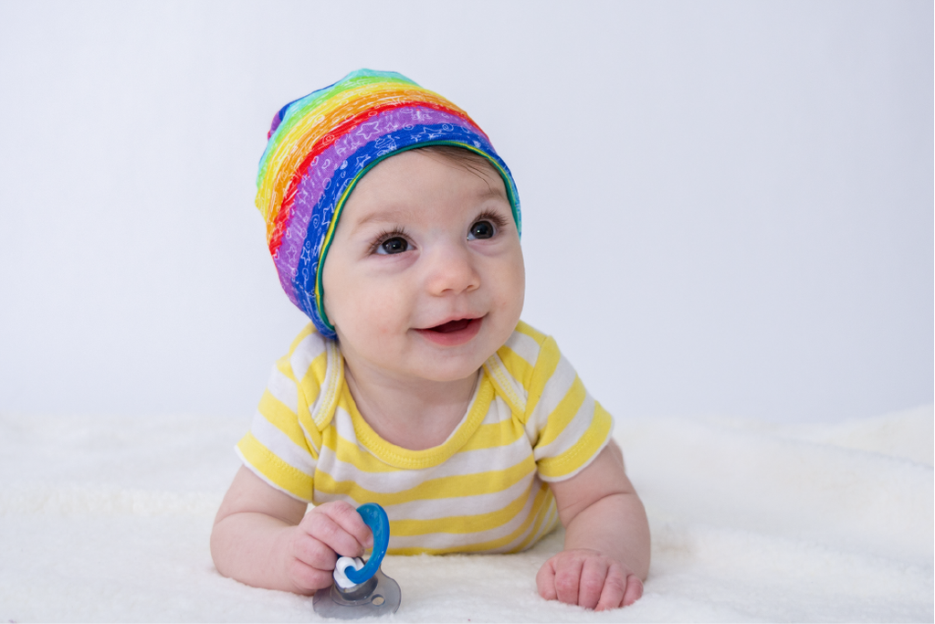 white baby wearing a rainbow beanie, holding a pacifier, wearing a yellow striped body suit, laying on a white blanket with a white background