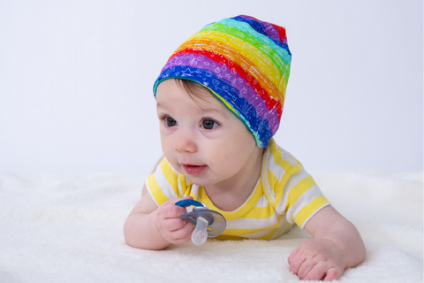 white baby wearing a rainbow beaning and holding a blue pacifier laying on a white blanket with a white background
