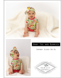 while baby on a white blanket wearing a floral bow and shirt with peach diaper cover