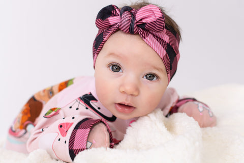 white baby girl laying on a sherpa blanket wearing a pink plaid knot headband