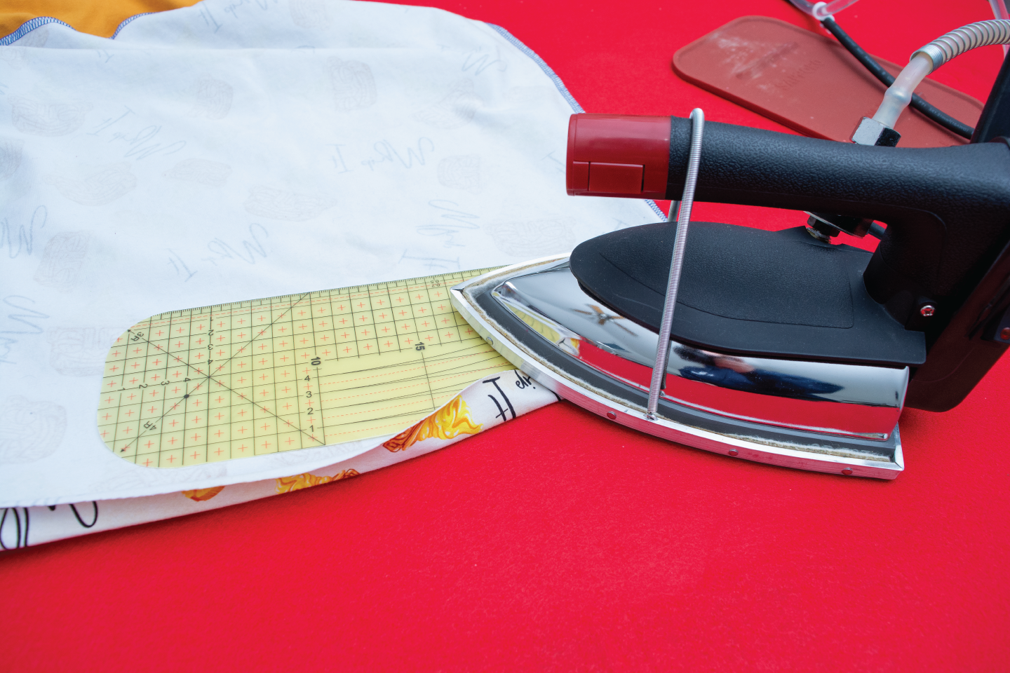 hot iron ruler being used to hem a dress with an iron