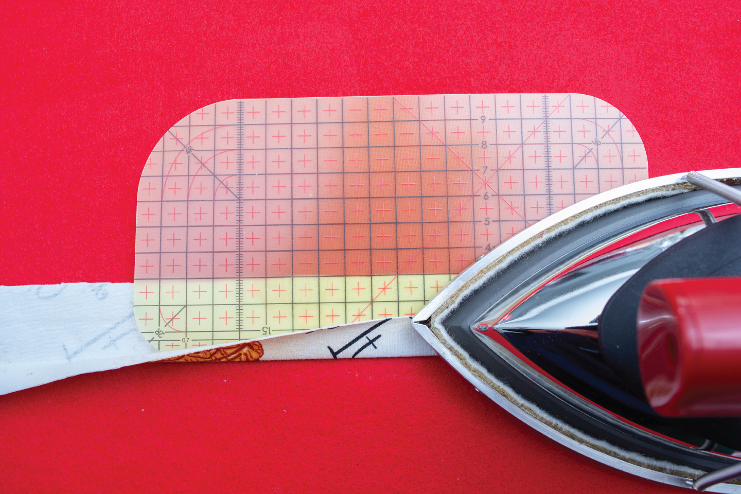 hot iron ruler being used on binding with an iron on a red background