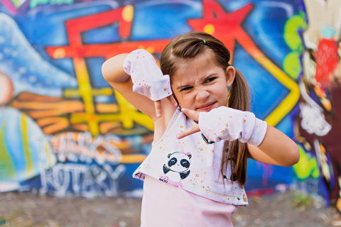 badass girl in front of graffiti wall with fingerless gloves on and a panda shirt