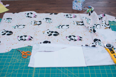 panda fabric on a sewing table next to embroidery scissors and a rotary cutter
