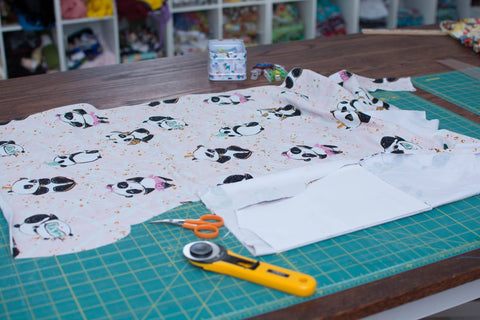 panda fabric on a cutting table with a cutting mat and rotary mat