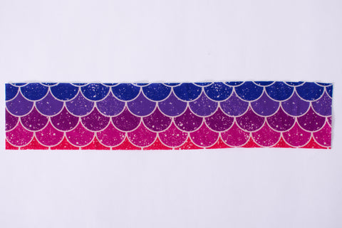 a pieces of rainbow mermaid scale fabric laying on a bright white background