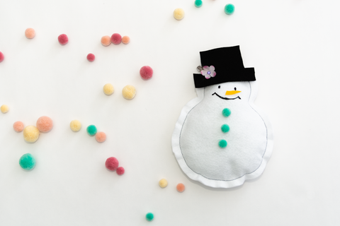 snowman with black top hat laying on white background surrounded by colorful pompoms