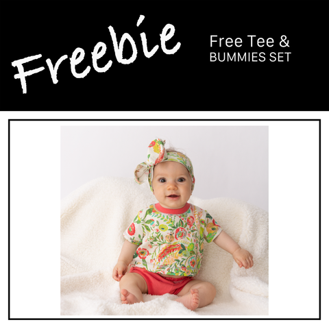 baby wearing floral tee and hair bow on white sherpa blanket