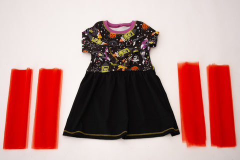 black and halloween fabric dress with 4 pieces of orange tulle laying on a white back drop