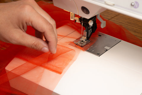 orange tulle laying on a sewing machine with a white person's hand holding the tulle