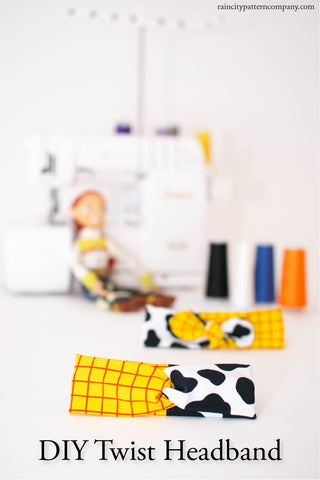 twist headband that is cow and checked print laying on a white background with a baby lock serger sitting behind it with 4 spools of thread and a toy story jessie doll