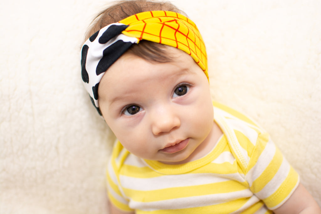 white baby wearing a yellow and white striped bodysuit and wearing a cow and checkered twist headband