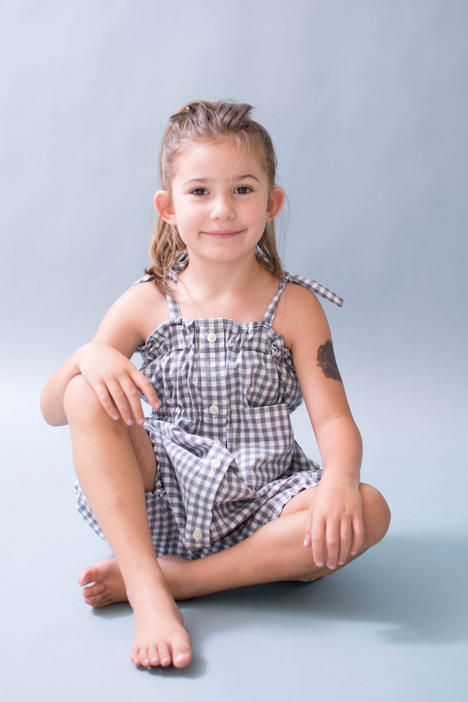 white girl with brown hair on white background wearing a checked romper with shoulder ties and buttons
